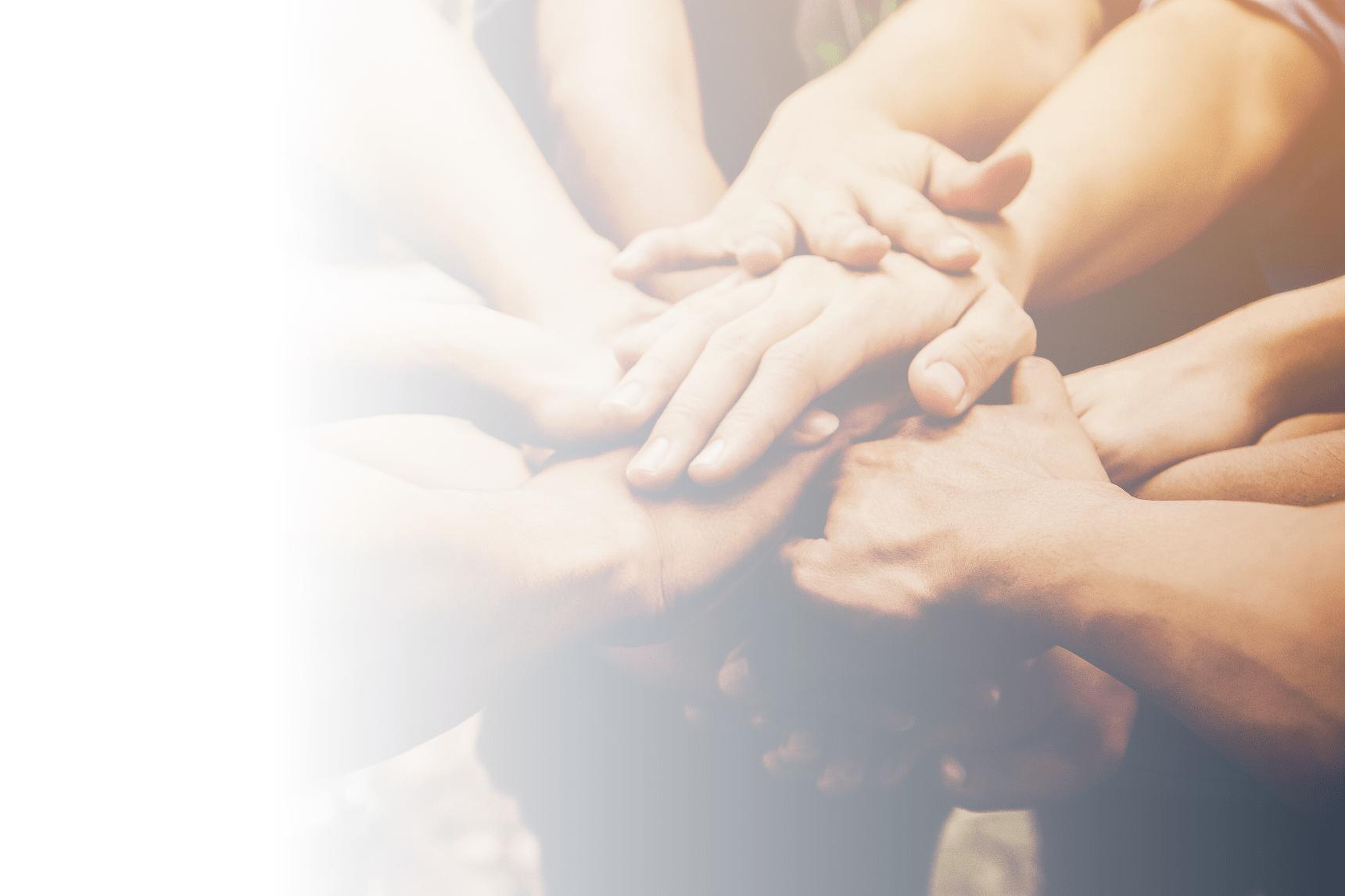 Mehrere Hände die Zusammenhalten - symbolisiert Mitarbeitermotivation durch das Team
